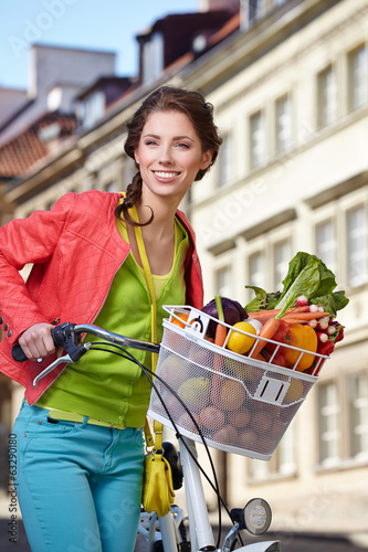 canvas print picture Pretty young woman with bicycle and groceries in old town street