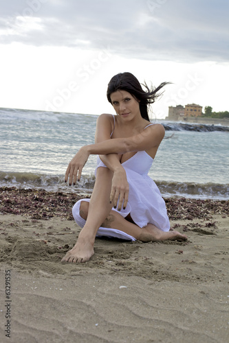 Happy smiling woman sitting on beach with wind