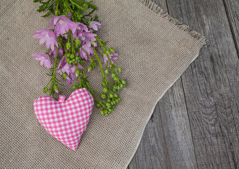 Rustic still life with a bouquet of pink mallow and heart