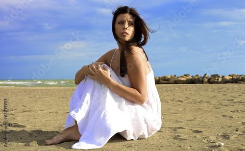 Woman posing with storm coming on beach