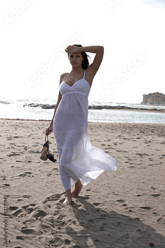 Woman with white dress in front of ocean with shoes in hand