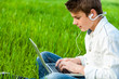 Teen working on laptop in green field.