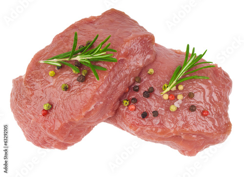 Raw ribeye steak garnished with a sprig of rosemary