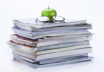 green apple and glasses on magazine and  book stack