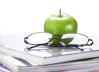 green apple and glasses on magazine and  book stack close up