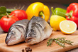 Sea fish prepared  for grill on the background of vegetables and
