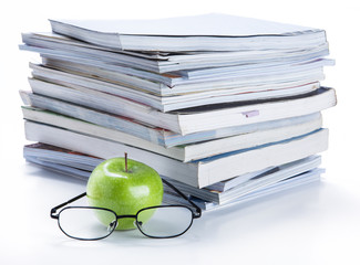 green apple and glasses with magazine and  book stack