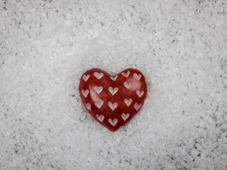 Red carved stone heart on snowy background