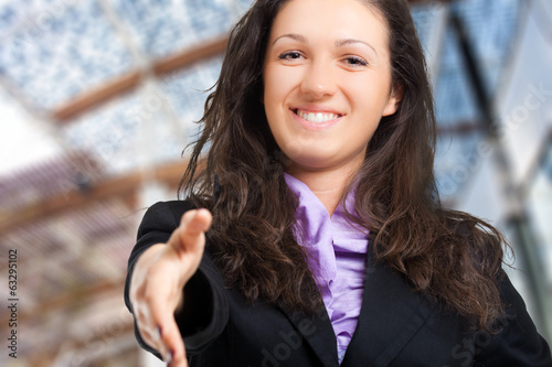 Cheerful businesswoman giving her hand