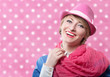 Laughing old-fashioned woman in a pink hat, polka dot background