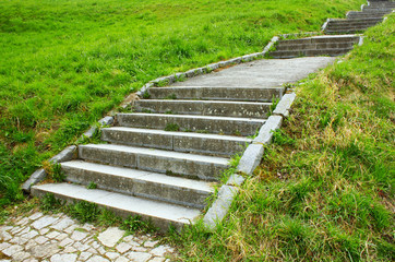 Stone stairway in green grass in a park