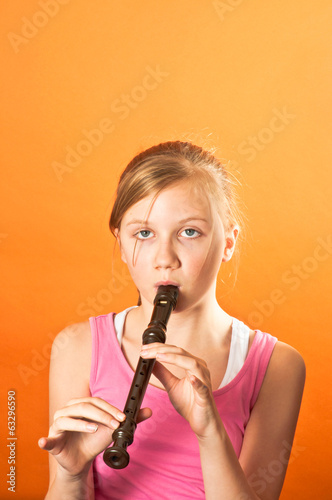 Pretty girl playing a recorder
