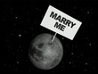 Message board on moon with the text words 'Marry me'.