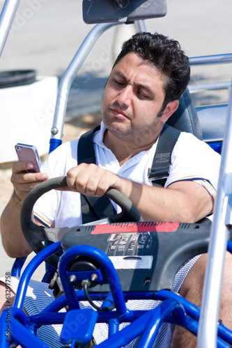 Man with mobile phone sits in buggy