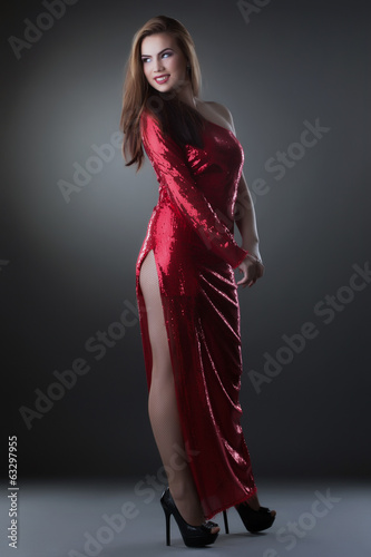 Curvy smiling woman posing in red long dress