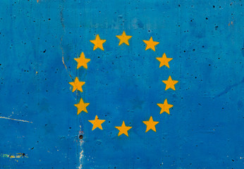 European Union flag on concrete wall.