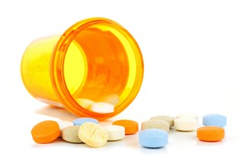 Pill bottle with spilling medicine tablets over white