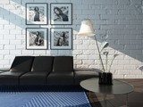 Living room interior with black leather couch against brick wall