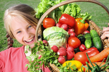 Smiling girl with basket of vegetables