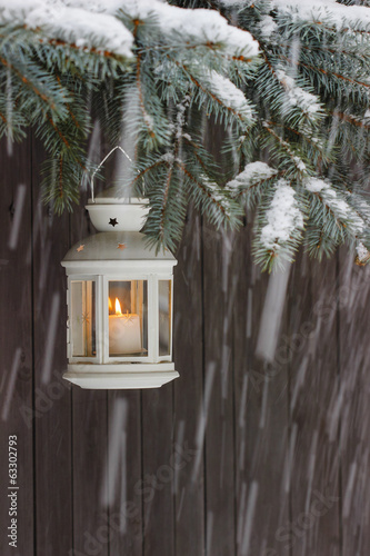 White lantern hanging on a fir branch.