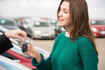 Woman receiving key outside in car dealership