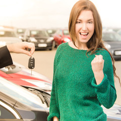 Excited woman receiving key in front of cars in dealership