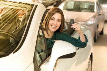Woman holding car key inside car dealership