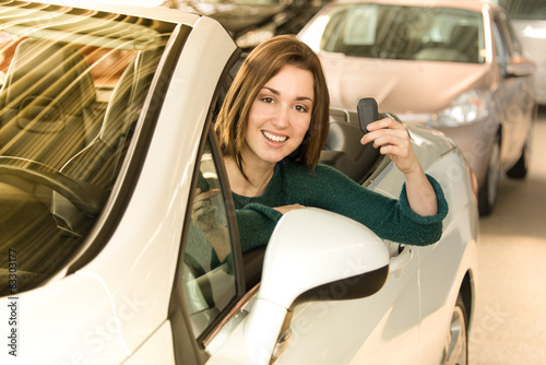 Woman holding car key inside car dealership