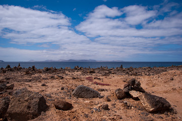 rock piles in playa blanca with fuerteventura island in the back