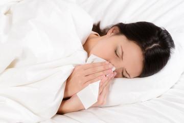 Kranke junge Frau putzt ihre Nase