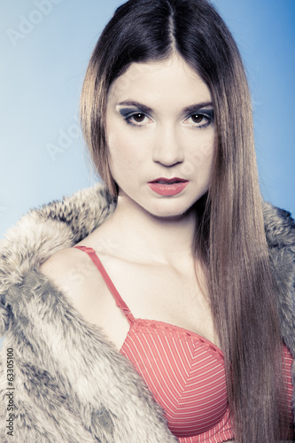 Sexy girl with long hair in red bra and fur coat on blue