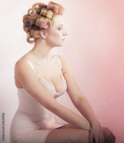 sexy pensive girl in underwear curlers preparing to party