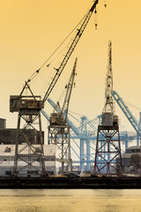 Commercial shipping cranes at sunset.Vertical.