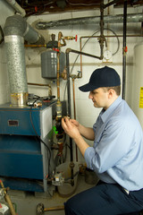 Service technician repairs furnace