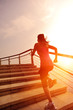 fitness young asian woman running sunrise seaside stairs