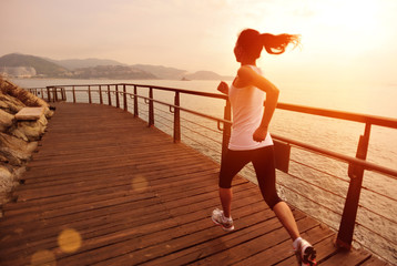 fitness young asian woman running sunrise seaside