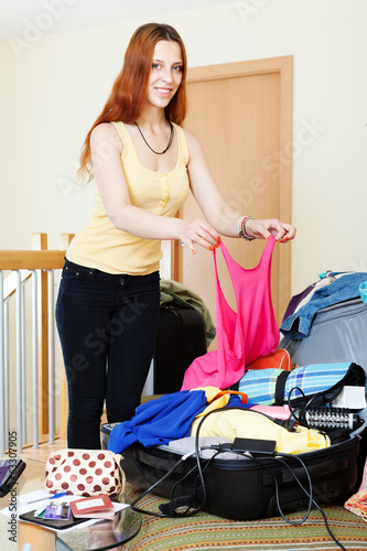red-haired woman adding clothes into suitcases