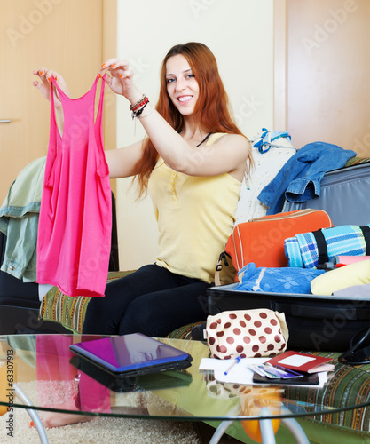 female traveler packing suitcase