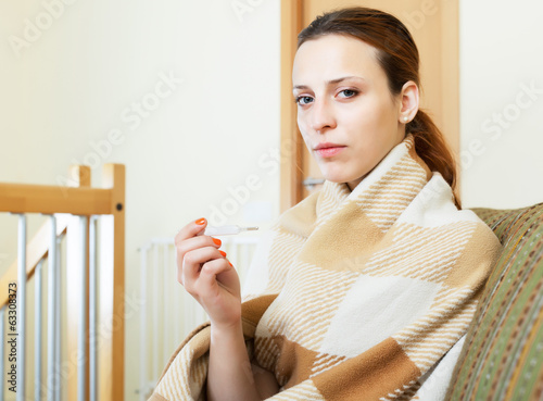 ordinary woman in plaid with thermometer