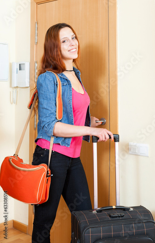 Red haired positive woman comes back home from vacation with bag
