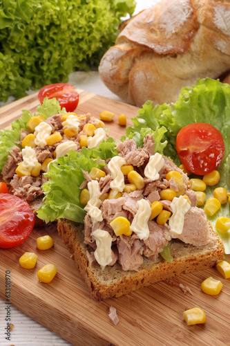 Sandwich with tuna, corn and tomato on wood