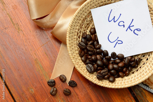 coffee beans in basket and wake up note on the wooden background