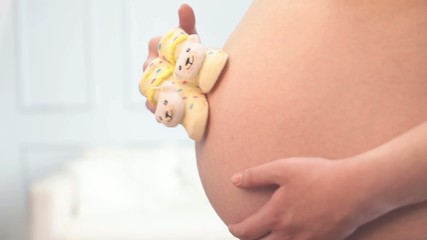 Woman is expecting a baby. Her belly is close-up