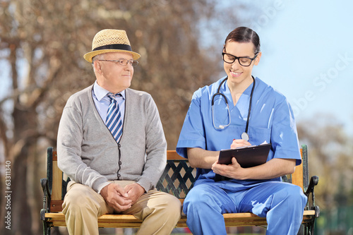 An elderly and a doctor sitting in park