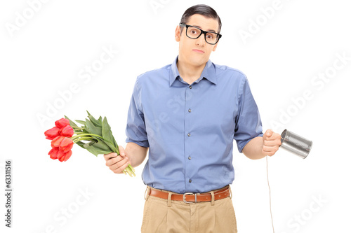 Confused man holding flowers and a tin can phone