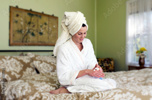 Young woman applies moisturiser to her skin