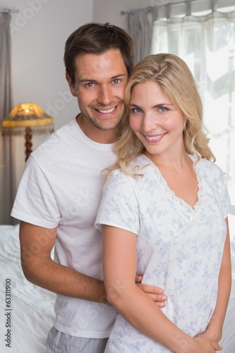 Smiling couple standing together at home