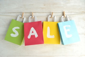 Colorful bargain sale shopping bags with clothes pins