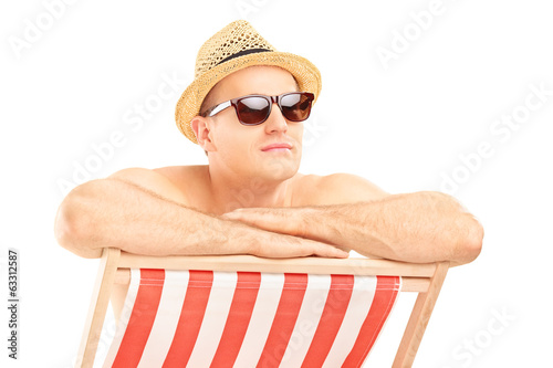 Man with sunglasses sitting on a sun lounger