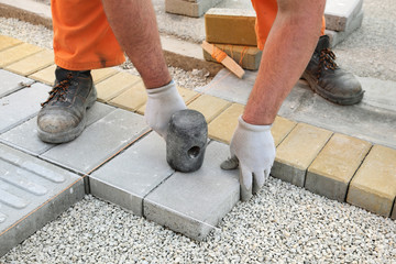 Construction site install of concrete brick pavement on gravel